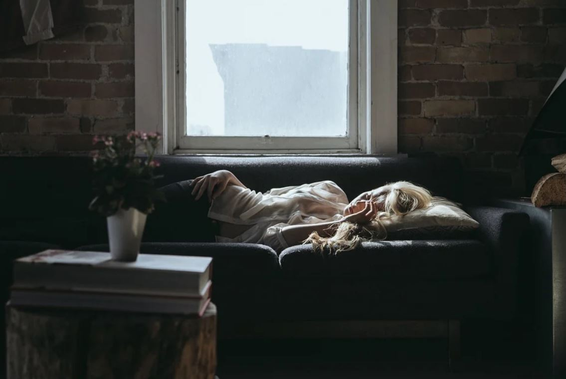 Picture of a tired woman lying on her sofa.