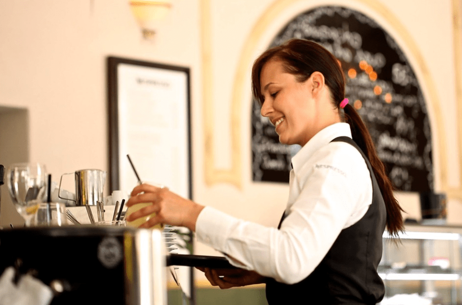 Picture of a waitress in a restaurant taking orders to serve.